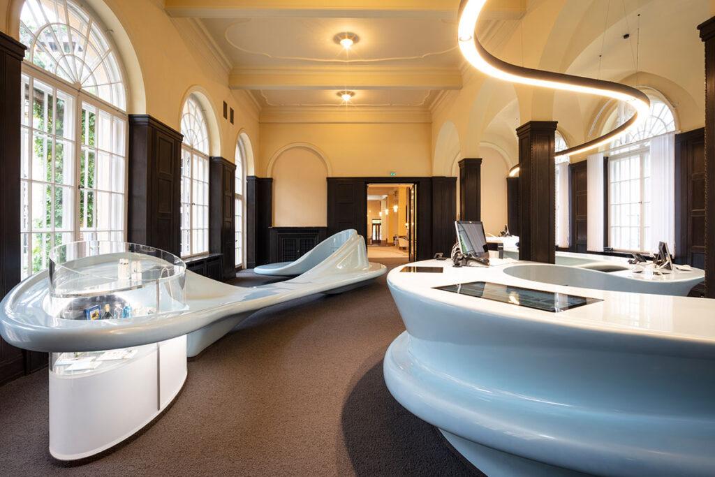 Dugi pultovi izrađeni od Corian® Solid Surface koji se tekućim oblicima vijugaju po sobi i predstavljaju vodu